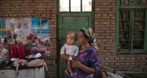 TURPAN, CHINA - SEPTEMBER 12: (CHINA OUT) A Uyghur woman holds a child in her home as they prepare food during the Corban Festival on September 12, 2016 in Turpan County, in the far western Xinjiang province, China. The Corban festival, known to Muslims worldwide as Eid al-Adha or 'feast of the sacrifice', is celebrated by ethnic Uyghurs across Xinjiang, the far-western region of China bordering Central Asia that is home to roughly half of the country's 23 million Muslims. The festival, considered the most important of the year, involves religious rites and visits to the graves of relatives, as well as sharing meals with family. Although Islam is a 'recognized' religion in the constitution of officially atheist China, ethnic Uyghurs are subjected to restrictions on religious and cultural practices that are imposed by China's Communist Party. Ethnic tensions have fueled violence that Chinese authorities point to as justification for the restrictions.  (Photo by Kevin Frayer/Getty Images)